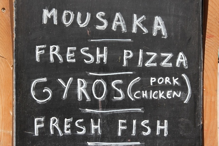 greek cuisine: Restaurant menu in Crete island - Greek cuisine blackboard. Stock Photo