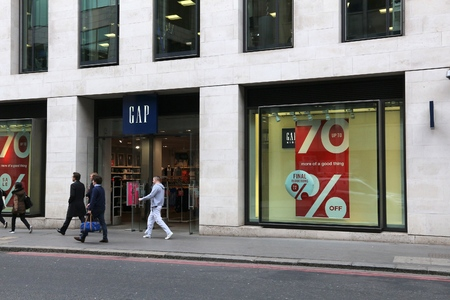 retailer: LONDON, UK - APRIL 22, 2016: People shop in the Gap in London, UK. Fashion retailer Gap exists since 1969 and has 3,076 stores worldwide. Editorial