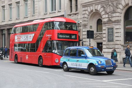 double decker: LONDON, UK - APRIL 22, 2016: People ride New Routemaster bus behind a taxi cab in City of London. The hybrid diesel-electric bus is a new, modern version of iconic double decker.