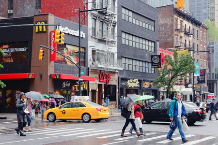 NEW YORK, UNITED STATES - JUNE 10, 2013: Pedestrians cross rainy 8th Avenue in New York. Almost 19 million people live in New York City metropolitan area.
