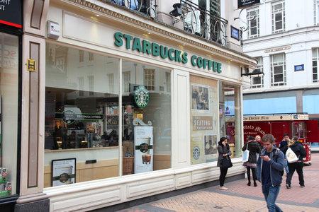 starbucks coffee: BIRMINGHAM, UK - APRIL 19, 2013: People walk by Starbucks Coffee cafe in Birmingham, UK. Starbucks Corporation operates 23,768 places worldwide.