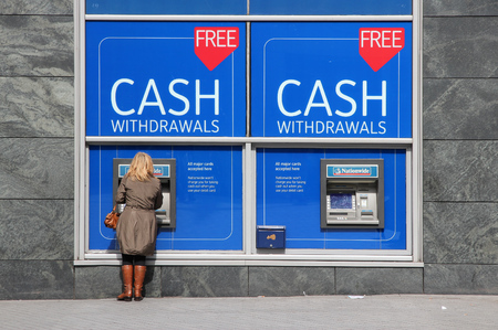 nationwide: BIRMINGHAM, UK - APRIL 19, 2013: Person withdraws cash in Nationwide ATM in Birmingham, UK. Nationwide Building Society Group has 193.3 billion GBP in assets (2013). Editorial