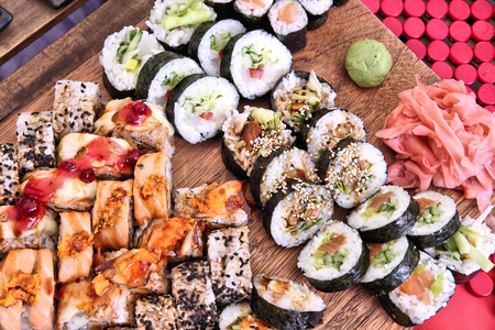 Sushi board with various nigiri, futomaki, hosomaki and uramaki rolls. Japanese cuisine.