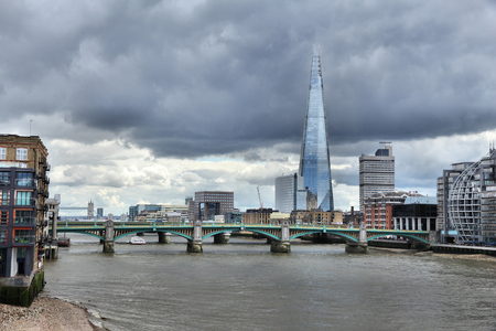 southwark: London skyline with storm clouds - city view with Southwark Bridge.