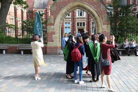 redbrick: LEEDS, UK - JULY 12, 2016: Graduates cheer at graduation day at the University of Leeds, UK. The redbrick university has some 32,000 students. Editorial