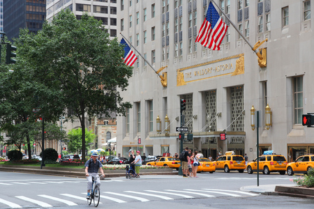 taxi famous building: NEW YORK, USA - JULY 4, 2013: People visit The Waldorf-Astoria hotel in New York. Waldorf Astoria is part of Hilton Worldwide, the group that manages 4,660 locations. Editorial