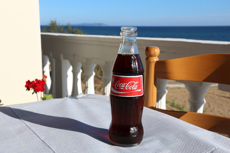 coke bottle: CORFU, GREECE - JUNE 4, 2016: Coca-Cola bottle at an outdoor restaurant in Corfu, Greece. Coca-Cola is distributed in almost every country in the world (Cuba in North Korea excluded).