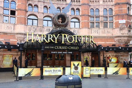 cursed: LONDON, UK - JULY 6, 2016: People walk by Palace Theatre in London, UK. The theatre promotes Harry Potter and the Cursed Child play.