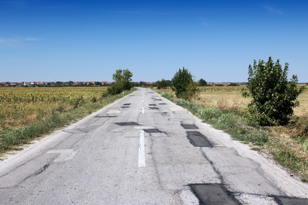 poorly: Poorly patched road in Negotin, Serbia. Regional road in Bor district of Serbia. Serbian countryside.