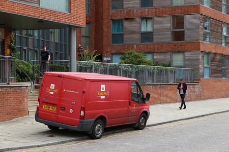 royal mail: LEEDS, UK - JULY 12, 2016: People walk by Royal Mail van in Leeds, UK. Royal Mail was founded in 1516. It employs 160,000 people.