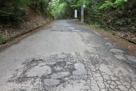 blacktop: Road damage in Japan - cracked asphalt blacktop with potholes and patches Stock Photo