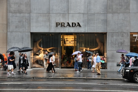 prada: NEW YORK, USA - JULY 1, 2013: People walk by Prada fashion shop at 5th Avenue, New York. 5th Avenue is ranked the most expensive retail area (per square foot) in the world.