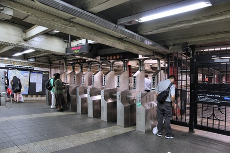 schlagbaum: NEW YORK, USA - JULY 1, 2013: People enter a subway station in New York. With 1.67 billion annual rides, New York City Subway is the 7th busiest metro system in the world.