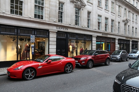 car retailer: LONDON, UK - JULY 6, 2016: People shop at Savile Row in London. Savile Row is a street in Mayfair, traditionally known for tailors.