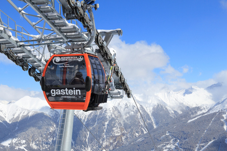ski runs: BAD GASTEIN, AUSTRIA - MARCH 9, 2016: People ride gondolas of cable car in Bad Gastein. It is part of Ski Amade, one of largest ski regions in Europe with 760km of ski runs.