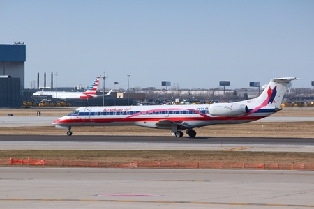 american airlines: CHICAGO, UNITED STATES - APRIL 1, 2014: American Eagle Embraer taxies after landing at OHare Airport in Chicago. AE is a part of American Airlines Group.
