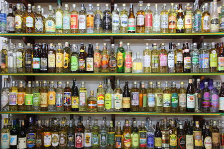 distilled: PARATY, BRAZIL - OCTOBER 14, 2014: Cachaca alcohol bottles collection in Brazil. Cachaca is a distilled spirit made of sugarcane juice, traditional for Brazil.
