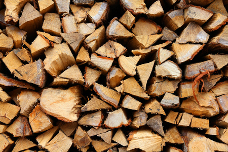 logs: Stacked firewood - pile of chopped fire wood logs. Rural background.