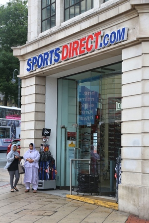 wares: LEEDS, UK - JULY 11, 2016: People walk by Sports Direct store in Leeds, UK. Sports Direct offers discount sports wares in 670 stores worldwide.