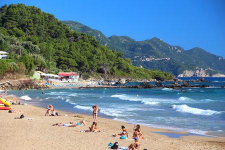 CORFU, GREECE - JUNE 3, 2016: People enjoy the beach in Pelekas, Corfu Island, Greece. 558,000 tourists visited Corfu in 2012.