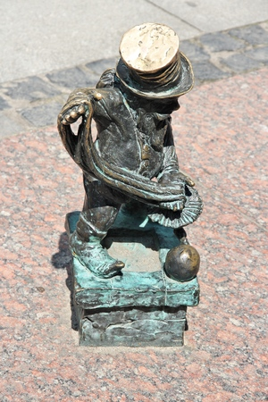 WROCLAW, POLAND - JULY 6, 2014: Dwarf or gnome small statue at Wroclaw Railway Station in Poland. Wroclaw has 315 gnome sculptures around the city. Editorial