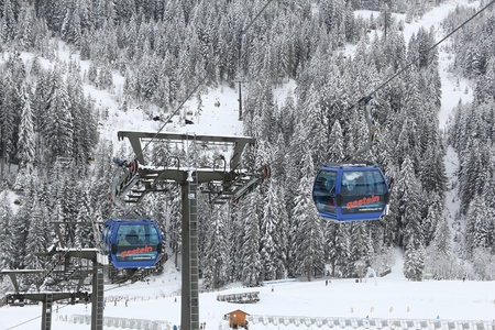 ski runs: BAD HOFGASTEIN, AUSTRIA - MARCH 7, 2016: People ride gondolas of cable car in Bad Hofgastein. It is part of Ski Amade, one of largest ski regions in Europe with 760km of ski runs. Editorial