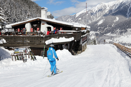 ski runs: BAD HOFGASTEIN, AUSTRIA - MARCH 9, 2016: People ski by apres ski restaurant in Bad Hofgastein. It is part of Ski Amade, one of largest ski regions in Europe with 760km of ski runs. Editorial