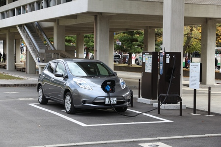 nissan: NARA, JAPAN - NOVEMBER 23, 2016: Nissan Leaf electric car charging at a station in Nara, Japan. Zero-emissions vehicles have improved vastly in recent years.