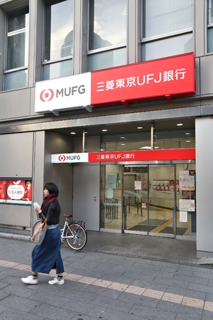 TOKYO, JAPAN - DECEMBER 1, 2016: Person exits MUFG Bank branch in Tokyo, Japan. MUFG full name is The Bank of Tokyo-Mitsubishi UFJ. It has 772 branches in Japan.