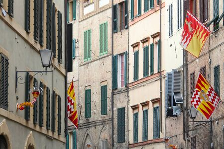 distinct: Siena, Italy. Old Town is divided into traditional districts (contrade) with distinct flags and colors. Valdimontone (Valley of the Ram). Stock Photo