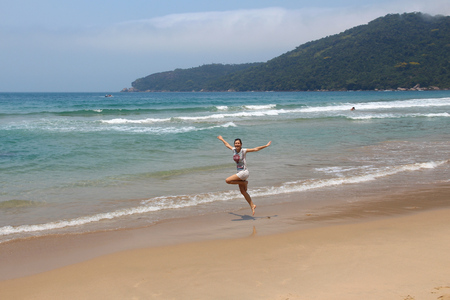 Brazil vacation - happy woman jumping on a sandy beach in Rio de Janeiro state.