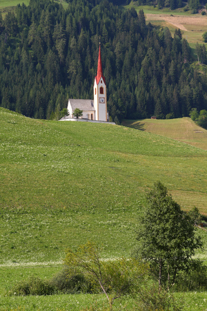 Italy - alpine village church in Prato Alla Drava. Small town with green pastures and Alps in background. Puster Valley in Trentino region.