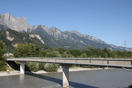Footbridge: Footbridge over Rhine river in Switzerland. Mountain landscape. Stock Photo
