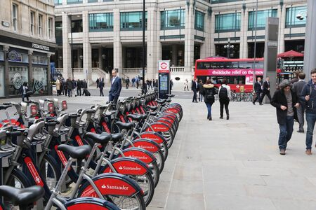 shared sharing: LONDON, UK - APRIL 22, 2016: People walk by Santander Bikes in the City of London. The public bike hire network has 839 stations and 13,600 bicycles. Editorial
