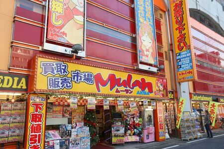 specializes: TOKYO, JAPAN - DECEMBER 4, 2016: People shop at Mulan Akiba store in Akihabara district of Tokyo, Japan. Mulan Akiba specializes in anime and video games.