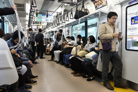 TOKYO, JAPAN - DECEMBER 3, 2016: People ride JR East Train in Tokyo. East Japan Railway Company employs more than 70,000 people. Редакционное