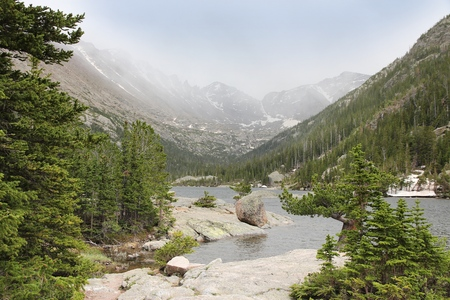shroud: Mills Lake with misty Rocky Mountains in background. Landscape in Colorado, USA.