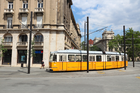 BUDAPEST, HUNGARY - JUNE 19, 2014: People ride orange tram in Budapest. It is part of BKK public transport system which serves 1.4 billion annual rides (2011). Editorial