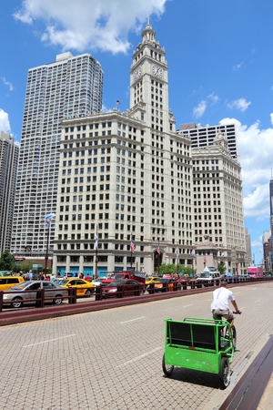 CHICAGO, USA - JUNE 28, 2013: Bicycle taxi rides by Wrigley Building in Chicago. The building was completed in 1924 and is 130m tall. It is clad in glazed terra-cotta.