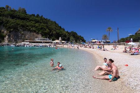 paleokastritsa: CORFU, GREECE - JUNE 2, 2016: People enjoy the beach in Paleokastritsa, Corfu Island, Greece. 558,000 tourists visited Corfu in 2012.