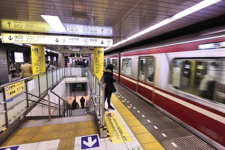 oshiage: TOKYO, JAPAN - NOVEMBER 30, 2016: People board Toei Subway train at Oshiage station in Tokyo, Japan. With more than 3.1 billion annual passenger rides, Tokyo subway system is the busiest in the world. Editorial