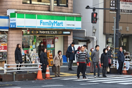 TOKYO, JAPAN - DECEMBER 1, 2016: People walk by FamilyMart convenience store in Tokyo, Japan. FamilyMart is one of largest convenience store franchise chains in Japan with 7,604 shops (2012).