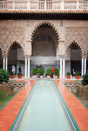 SEVILLE, SPAIN - NOVEMBER 4, 2012: People visit Royal Alcazar in Seville, Spain. Seville is a major tourism destination in Spain with 4.8 million hotel-nights in 2011.