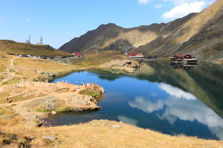 FAGARAS MOUNTAINS, ROMANIA - AUGUST 23, 2012: People visit mountain hostel and Lake Balea in Fagaras Mountains, Romania. This tourist area is located at an altitude of 2,042 metres. Editorial