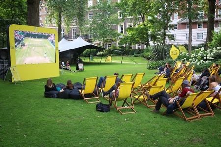 LONDON, UK - JULY 7, 2016: People enjoy public Wimbledon tennis tournament broadcast in Grosvenor Square park of London, UK.