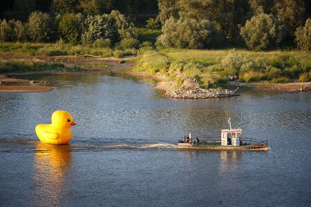 WARSAW, POLAND - JUNE 18, 2016: Yellow large inflatable duck tugged on Wisla River in Warsaw. It promoted a local company Duckie Deck.