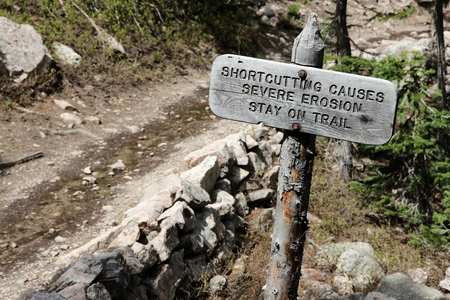 National park sign: trail shortcutting causes severe erosion. Stay on trail! Rocky Mountains National Park, Colorado. Banco de Imagens