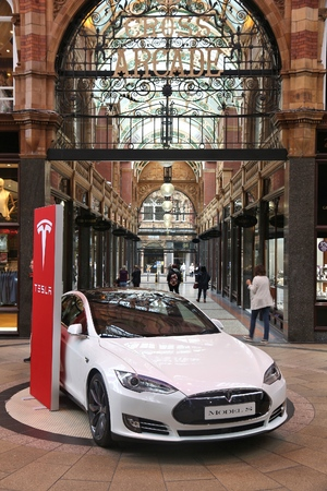 LEEDS, UK - JULY 11, 2016: People walk by Tesla Model S electric car in Leeds, UK. Tesla Motors is one of biggest manufacturers of electric vehicles in the world.