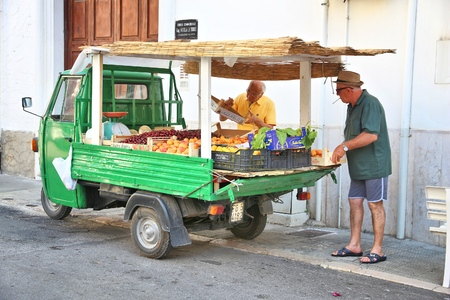 VIESTE, ITALY - JUNE 5, 2017: Vendor sells fruit from an old Piaggio truck in Vieste. Mobile fruit and vegetable shops are popular in Italy.