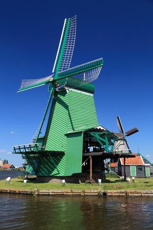 Windmill in Netherlands. Old industrial architecture in Zaanse Schans rural area in Zaandam.
